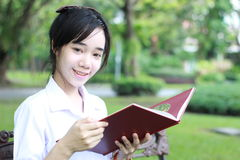 La muchacha hermosa adolescente del estudiante tailandés leyó un libro que se sentaba en parque Imagenes de archivo