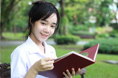 La muchacha hermosa adolescente del estudiante tailandés leyó un libro que se sentaba en parque Imagen de archivo