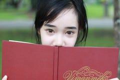 La muchacha hermosa adolescente del estudiante tailandés leyó un libro que se sentaba en parque Fotografía de archivo libre de regalías