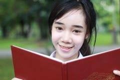 La muchacha hermosa adolescente del estudiante tailandés leyó un libro que se sentaba en parque Fotografía de archivo
