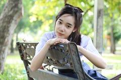 La muchacha hermosa adolescente del estudiante tailandés se relaja y sonríe en parque Fotografía de archivo libre de regalías