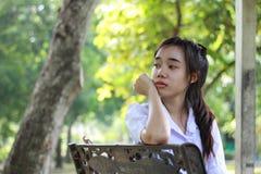 La muchacha hermosa adolescente del estudiante tailandés se relaja y sonríe en parque Fotografía de archivo