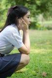 La muchacha hermosa adolescente del estudiante tailandés se relaja y sonríe en parque Imagen de archivo libre de regalías