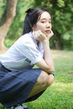 La muchacha hermosa adolescente del estudiante tailandés se relaja y sonríe en parque Foto de archivo