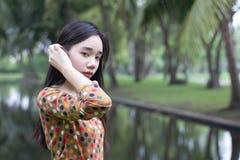 La muchacha hermosa adolescente del estudiante tailandés se relaja y sonríe en parque Imagenes de archivo