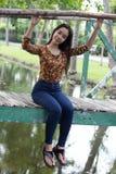 La muchacha hermosa adolescente del estudiante tailandés se relaja y sonríe en parque Fotos de archivo