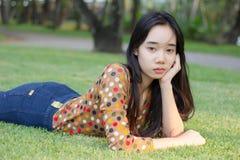 La muchacha hermosa adolescente del estudiante tailandés se relaja y sonríe en parque Imágenes de archivo libres de regalías