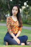La muchacha hermosa adolescente del estudiante tailandés se relaja y sonríe en parque Fotos de archivo libres de regalías