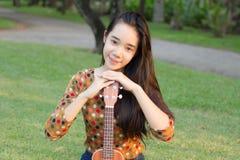 La muchacha hermosa adolescente del estudiante tailandés se relaja y sonríe en parque Imagen de archivo