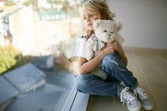 La muchacha hermosa adolescente en vaqueros viste cerca de la ventana con el oso Imágenes de archivo libres de regalías