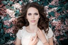 La muchacha hermosa adolescente que miente en lila florece el fondo Ascendente cercano del retrato imagenes de archivo