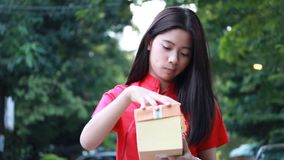 La muchacha hermosa adolescente tailandesa en chino se viste, Feliz Año Nuevo y abre el regalo de la caja, infeliz