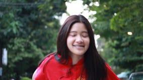 La muchacha hermosa adolescente tailandesa en chino se viste, Feliz Año Nuevo y da el regalo, se relaja y sonríe