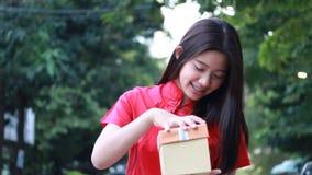 La muchacha hermosa adolescente tailandesa en chino se viste, Feliz Año Nuevo y regalo abierto de la caja, sonrisa y muy feliz