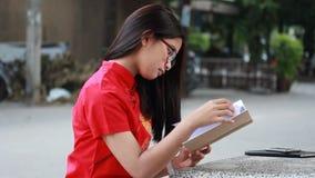 La muchacha hermosa adolescente tailandesa en chino se viste leyó un libro almacen de metraje de vídeo