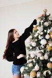 La muchacha hermosa adorna el árbol de navidad Fotos de archivo libres de regalías