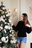 La muchacha hermosa adorna el árbol de navidad Foto de archivo libre de regalías