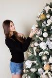 La muchacha hermosa adorna el árbol de navidad Imagen de archivo libre de regalías