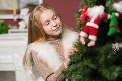 La muchacha hermosa adorna los juguetes de un árbol de navidad Imagen de archivo libre de regalías