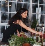 La muchacha hermosa adorna la tabla para la Navidad y la pieza central del árbol de hoja perenne Imágenes de archivo libres de regalías