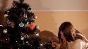 La muchacha hermosa adorna un árbol de navidad con los juguetes almacen de video
