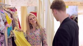 La muchacha hermosa adulta joven con su prometido elige la ropa con una sonrisa almacen de metraje de vídeo