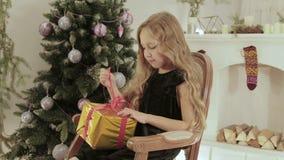 La muchacha hermosa, alegre abre su regalo en el fondo del árbol de navidad metrajes