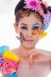 La muchacha hermosa asiática con colorido compone con las flores frescas y la mariposa Imágenes de archivo libres de regalías