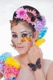 La muchacha hermosa asiática con colorido compone con las flores frescas y la mariposa Imagen de archivo