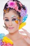 La muchacha hermosa asiática con colorido compone con las flores frescas y la mariposa Imagen de archivo libre de regalías