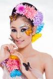 La muchacha hermosa asiática con colorido compone con las flores frescas y la mariposa Fotos de archivo