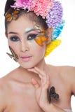 La muchacha hermosa asiática con colorido compone con las flores frescas y la mariposa Fotografía de archivo libre de regalías