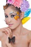 La muchacha hermosa asiática con colorido compone con las flores frescas y la mariposa Imagenes de archivo