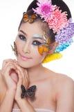 La muchacha hermosa asiática con colorido compone con las flores frescas y la mariposa Fotografía de archivo