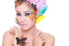 La muchacha hermosa asiática con colorido compone con las flores frescas y la mariposa Foto de archivo libre de regalías