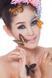 La muchacha hermosa asiática con colorido compone con las flores frescas y la mariposa Foto de archivo