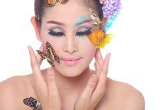La muchacha hermosa asiática con colorido compone con las flores frescas y la mariposa Fotos de archivo libres de regalías