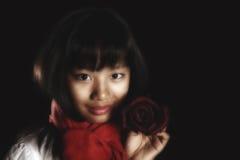 La muchacha hermosa asiática con una sonrisa sostiene Borgoña subió Fotos de archivo