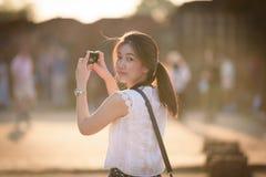 La muchacha hermosa asiática tiene viaje y toma una foto en el templo de Wat Chaiwatthanaram en Ayuthaya, Tailandia imagen de archivo libre de regalías