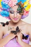 La muchacha hermosa asiática con colorido compone con las flores y la mariposa frescas del crisantemo Fotos de archivo