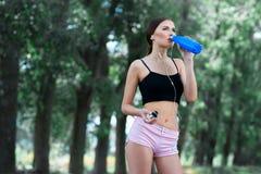 La muchacha hermosa bebe el agua después de activar Imagen de archivo