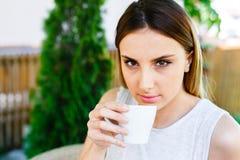 La muchacha hermosa bebe el café mientras que se sienta en el jardín del ` s del café Fotos de archivo
