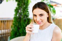La muchacha hermosa bebe el café mientras que se sienta en el jardín del ` s del café Imagen de archivo
