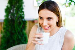 La muchacha hermosa bebe el café mientras que se sienta en el jardín del ` s del café Fotos de archivo libres de regalías