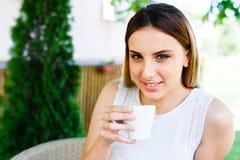 La muchacha hermosa bebe el café mientras que se sienta en el jardín del ` s del café Foto de archivo