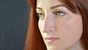 La muchacha hermosa blanca con el pelo rojo y los ojos verdes con extensiones de la pestaña en un fondo oscuro mira seriamente a  foto de archivo libre de regalías