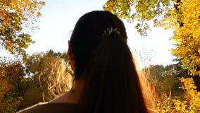 La muchacha hermosa camina en el bosque del otoño que los rayos brillantes del sol brillan en la lente de cámara Primer metrajes