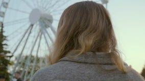 La muchacha hermosa camina a lo largo del parque de la atracción en una capa en colores pastel elegante almacen de video