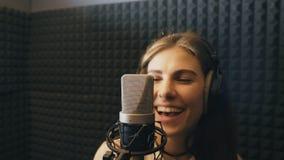 La muchacha hermosa canta en estudio de los sonidos y proceso del goce Cantante joven que registra emocionalmente la nueva canció metrajes