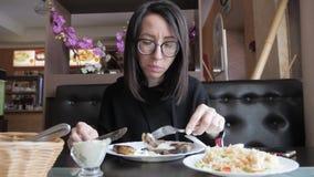 La muchacha hermosa cena en el restaurante, comiendo el plato caliente servido delicioso cenando muy bien almacen de video